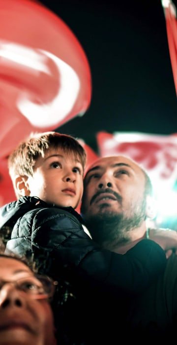 Image: A man holds a child as they wait for President Erdogan t appear for a speech at the AKP headquarters in Istanbul, on April 16.