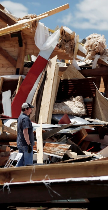 Image: Kris Ingram, a DJ hired to perform at a prom at The Rustic Barn, looks through debris for his equipment after the event venue sustained major tornado damage, in Canton, Texas