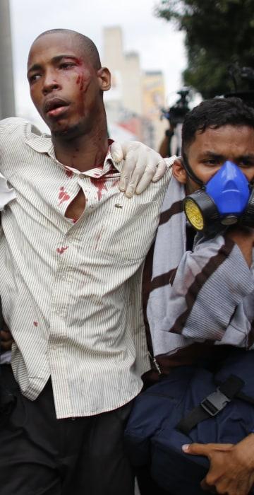 Image: Paramedics assist a man injured during clashes, April 20, 2017.