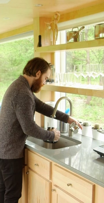 Seth Porges makes breakfast in his tiny house in the Hudson Valley, NY.