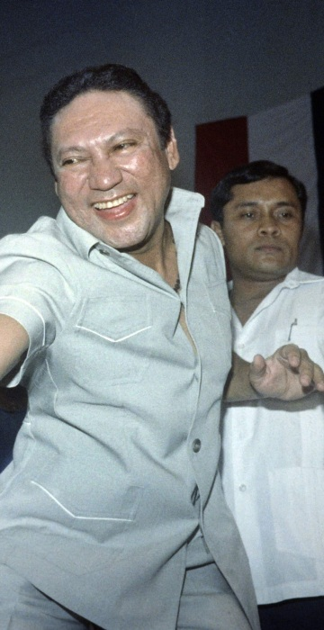 Image:  General Manuel Antonio Noriega reaching down to shake the hands of followers who attended Noriega's birthday party