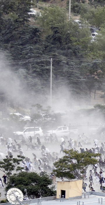 Image: Funeral goers break into a run after one of three suicide bombers detonated during the ceremony.