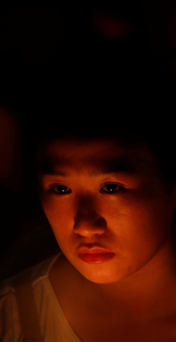 Image: A girl takes part in a candlelight vigil in Hong Kong