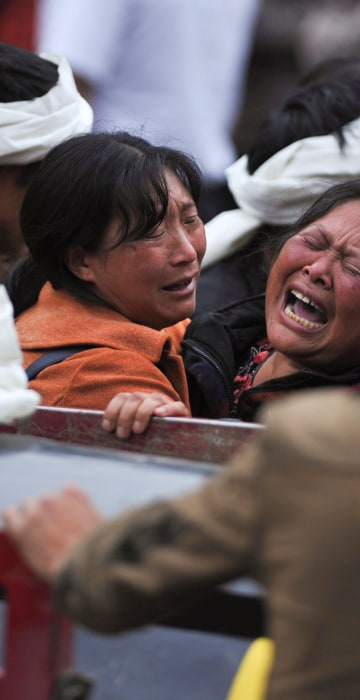 Image: Women become emotional at the site of the landslide on June 25.