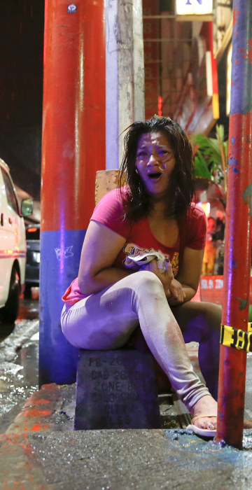 Image: A woman cries after her husband was shot dead by unidentified gunmen riding motorcycles in Manila