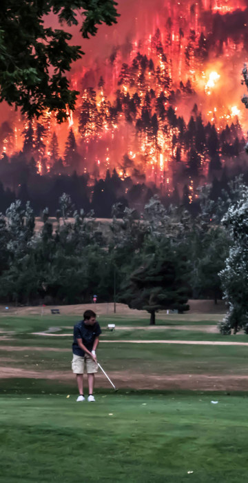 Image: Eagle Creek wildfire burns as golfers play at the Beacon Rock Golf Course in North Bonneville Washington