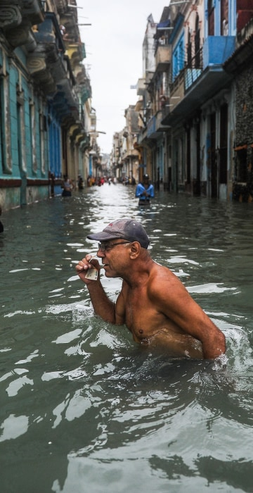 Image: A Cuban wades through a flooded street in Havana,