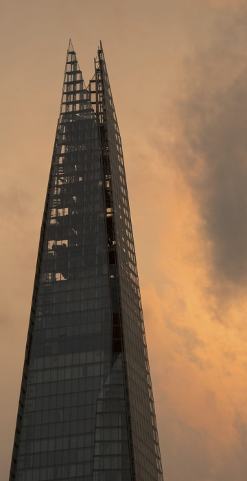 Image: A plane flies past the Shard in central London, as the sky takes on an unusual orange colour