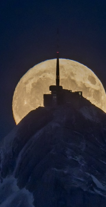 Image: The moon rises in front of the Saentis mountain near the village of Ebnat-Kappel, Switzerland