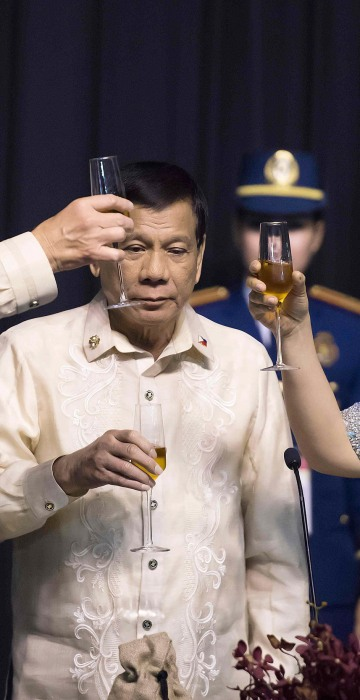Image: Philippine President Rodrigo Duterte stands as his partner Honeylet Avancena toasts Trump during the gala dinner on Nov. 12.