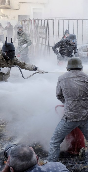 Image: Revelers dressed in mock military outfits battle with flour, eggs and firecrackers