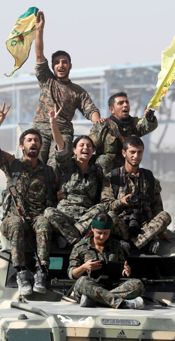 Image: Syrian Democratic Forces (SDF) fighters ride atop of military vehicles as they celebrate victory in Raqqa