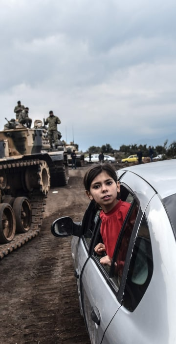 Image: A girl leans out of the window of a car to look as Turkish army tanks and soldiers gather close to the Syrian border
