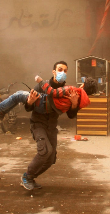 A member of the Syrian Civil Defence carries an injured child in Douma on Feb. 7.