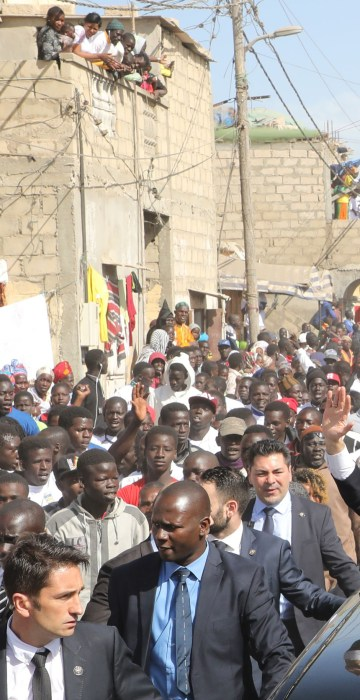 French President Emmanuel Macron and Senegalese President Macky Sall wave to the crowd in Saint-Louis on Feb. 3, the final day of Macron's visit to Senegal.