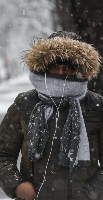 Image: A person walks through the snow during a storm in the Brooklyn borough of New York City