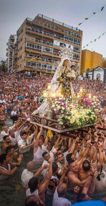 Image: Men unload a statue of the Virgin del Carmen after its journey to Puerto de la Cruz