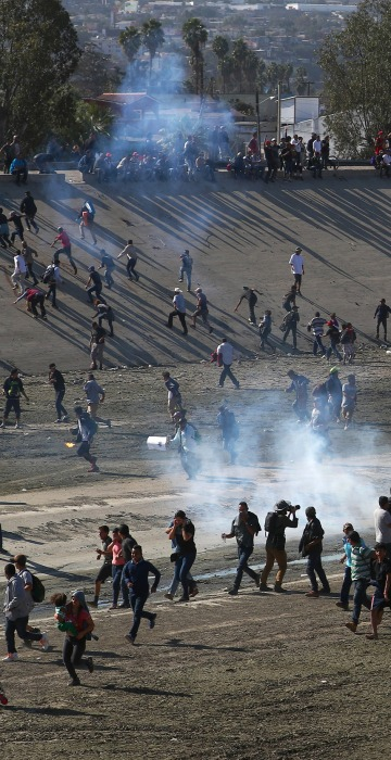 Image: Migrants run from tear gas, thrown by the U.S border patrol, near the border fence between Mexico and the United States in Tijuana