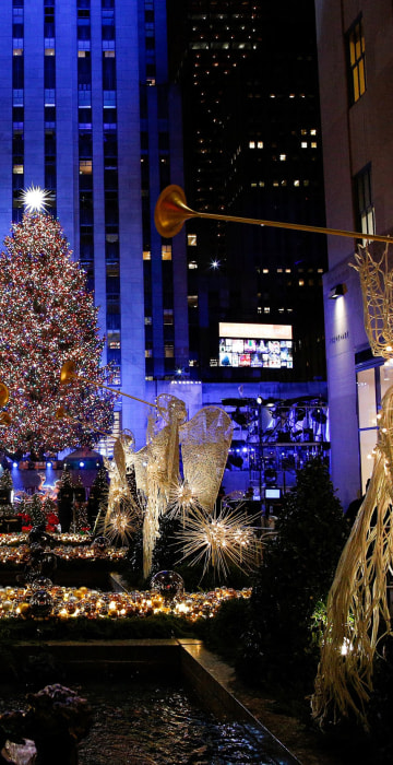 Image: People watch the Christmas tree lighting at Rockefeller Center in the Manhattan borough of
