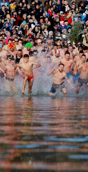 Image: Swimmers run into the chilly waters of Lake Balaton in Szigliget, Hungary.