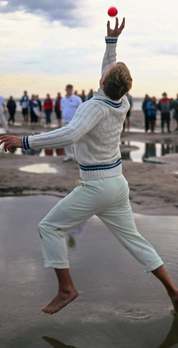 Image: A player participates in the annual Brambles Sandbank cricket match at low tide in the Solent
