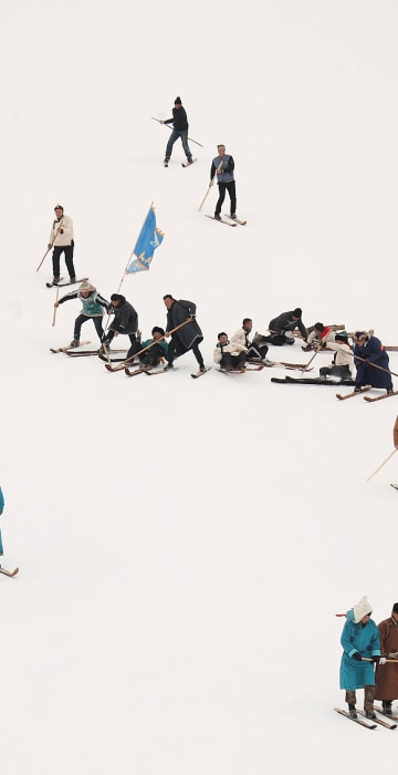 Image: People perform on traditional horsehide skis during an event to celebrate the origins of skiing at the Jiangjunshan ski resort in Altay