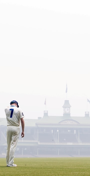 Image: Liam Hatcher of the Blues stands in the outfield amid the smoke haze from bushfires during day 3 of the Sheffield Shield cricket match between New South Wales and Queensland at the SCG in Sydney
