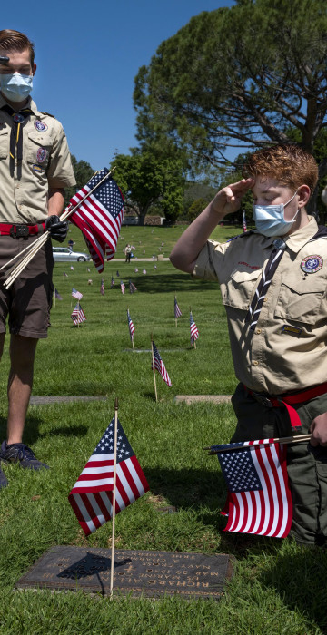 Image: Nathan Federoff and his brothers, Xander and Christian, scouts with the Tierra Rejada District, salute a grave at the Pierce Brothers Memorial Park in Los Angeles on May 23.