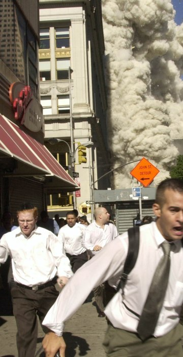 """Smoke and debris fill the streets as pedestrians run for cover after the collapse of the south tower. What started as a bright sunny day turned to darkness. """"Suddenly the top of [the tower] just shattered into tens of thousands of pieces,"""" said Steve Johnson of msnbc.com. """"You could see the whole thing just disappeared. Then the smoke came up. The cops started yelling, 'Get back! Run! Get Away!'  I ran inside a hotel, and it went black outside because of the dust."""""""