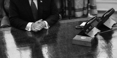 Image: Then-President Donald Trump is reflected on the Resolute Desk in the Oval Office at the White House in 2019.