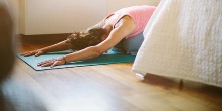 image: Mid adult woman in yoga position on bedroom floor