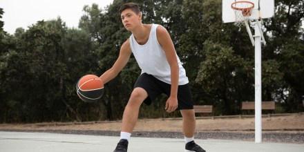Male teenage basketball player playing basketball on court