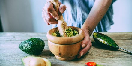 Close-up of hands making homemade guacamole