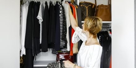 Woman hanging clothes in closet