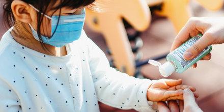 Parent applying hand sanitizer to childs hands in playground