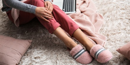 woman wearing slippers working from home on laptop