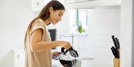 Woman pouring herself coffee from a coffee pot in the kitchen