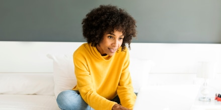 Smiling woman sitting on bed using laptop. Best sweater for women 2021 at Nordstrom, Amazon, Net-a-Porter, Gap, Uniqlo, L.L. Bean, Everlane and more. Best sweaters for women under $500. How do you maintain a sweater? How do you wash sweaters?
