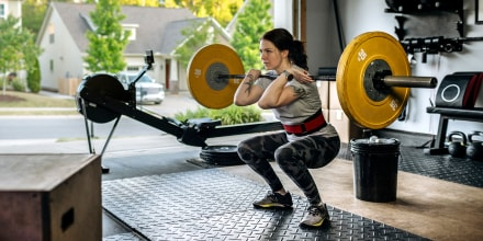 Fit woman performing front squat with heavy barbell in her home garage gym during covid-19 pandemic. Shop the best barbells for your home gym in 2021 shared by fitness experts and personal trainers, including Olympic barbells, Powerlifting barbells and mo