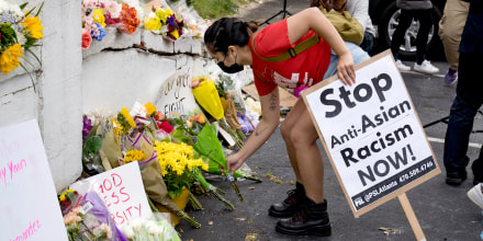 Image: Activists drop flowers during a demonstration against violence against women and Asians following Tuesday night's shooting on March 18, 2021 in Atlanta.