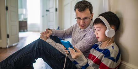 Father and son with white headphones on, sitting on floor in their hallway, watching an iPad