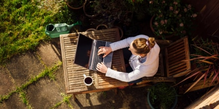 Woman sitting outside with a cup of coffee, surrounded by her garden, working on her laptop. Shop the best outdoor office ideas for working from home outside, including office furniture and accessories such as fans, umbrellas, laptop desks and more.