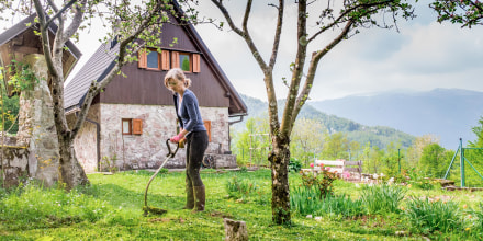 Woman trimming the weeds in her backyard