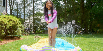 Little girl in her backyard, standing up on her blue waterslide as it squirts out water