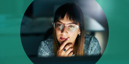 Woman looking at her computer at night, wearing blue light glasses. When shopping for the best blue light glasses, look for yellow lenses. Learn more about the benefits and shop the best blue light glasses.