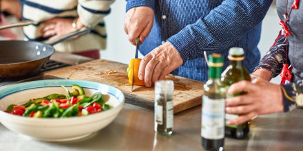 Man cutting a pepper on a wooden chopping board, surrounded by a salad and some olive oil