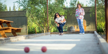 Two woman playing bocce ball outside, while holding wine. Shop the best outdoor games of 2021 to play with family and friends. The best backyard games here for adults and kids include corn hole, outdoor jenga and more.