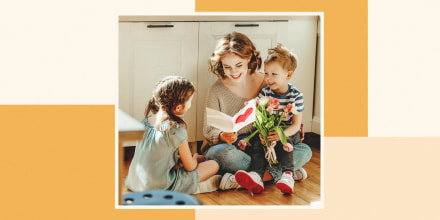 Woman sitting on her floor of the kitchen, with her son on her lap and her daughter nearby, reading a Mother's Day card