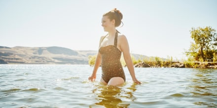 Smiling woman wading in river, wearing a one-piece swimsuit