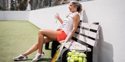 Woman holding water bottle while sitting on bench at tennis court, wearing trendy tennis shoes